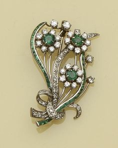 An emerald and diamond floral spray brooch  Designed as a scrolling openwork bouquet, each flowerhead set with a circular-cut emerald and brilliant-cut diamond cluster, accented by stems of baguette-cut emeralds and a ribbon bow of single-cut diamonds, total diamond weight approximately 0.65ct, length 4.9cm.
