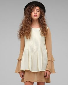 Pleated tunic over long-sleeved dress