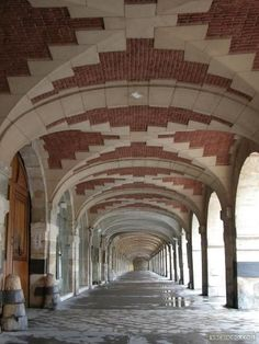 The arcades of the Place des Vosges, in the Marais, the oldest square in Paris