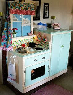 "Play Kitchen. Homemade from a recycled entertainment center or was it a nightstand curio cabinet? Click on ""Next"" at top of picture to see   ""Before"" picture. Love the real curtained window   with a view!"