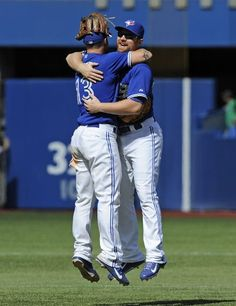 Brett Lawrie #13 and Adam Lind #26 of the Toronto Blue Jays celebrate the teams win over the Oakland Athletics during MLB game action August 10, 2013 at Rogers Centre in Toronto, Ontario, Canada. (Photo by Brad White/Getty Images)