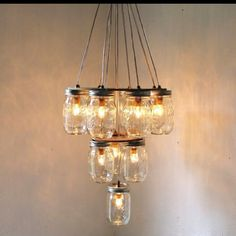 Mason Jar chandelier, using corded Christmas lights (like those used in a Christmas village display). Love the concept