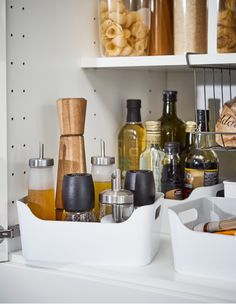 IKEA VARIERA smooth white plastic boxes are no-spill solutions for tall oil bottles and sauces, with handles that are easy to grab. Group condiments together for an organized and spill-proof pantry.