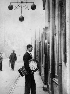 A man carries a large clock into a pawnbroker's, passing under the three balls which are the international symbol of this profession, 1931.