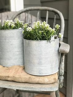 White alyssum tucked in large silver cans... would also look great if a little rusty.