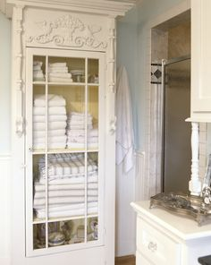 glass-front cabinet, painted yellow on the inside, is a distinctive way to display towels and linens ..