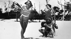 Young women playing a game of baseball on a beach in Miami, Florida.