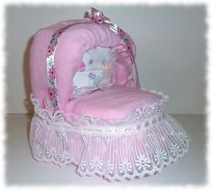 """Small Pink Bassinet Diaper Cake - 16 Huggies Snuggles diapers, size 2; 1 receiving blanket; 1 pink Gerber onesie, size 0-3 months; 2 pink burp cloths; lace; ribbon.     Approximate Dimensions and Weight:     7.3"""" long x 7.3"""" wide x 9"""" high; 1.4 lbs.     This cute pink bassinet diaper cake will serve as a terrific smaller baby shower centerpiece and baby shower gift or general gift for a new mom and baby girl.  $38.00"""