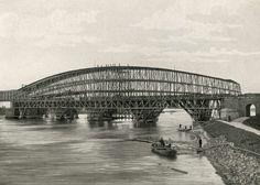 Bouw van de spoorbrug over de Lek bij Kuilenburg. De brug staat nog in de steigers en er lopen mensen boven over de bogen. Kuilenburg, Betuwe, Nederland, 1867.