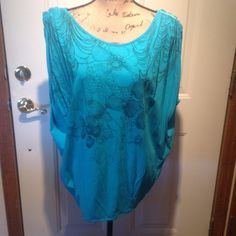 Turquoise Blouse Turquoise short sleeve blouse with black flowers on the front. The blouse gathers on the shoulders and ties in the back. There is a elastic band at the bottom. The tag is cut out because it scratchy on skin when worn. Tops Blouses