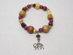 Bohemian style stretch bracelet with wooden beads, purple and silver accents and elephant charm.  The elephant symbolizes wisdom, strength and peace. by MyCreativeSideJewels on Etsy