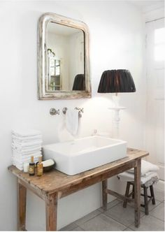 white beautiful bathroom, lovely touch with the lamp (though it's mot certainly does not provide enough light)