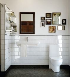 White Bathroom with gray pentagonal floor time, minimalish, clean, large tiled wall with dark grout