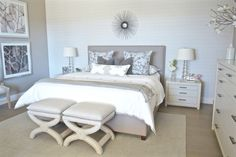 Neutral master bedroom inspiration sure to make you feel like you are at a hotel. A neutral beige upholstered bed is the best backdrop to add layers of color and patterned pillows. Shimmer wallpaper feature wall and large prints hanging on side wall. Master with white bedding and 2 benches at the foot of the bed.