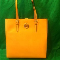 """Michael Kors Saffiano Jet Set Tote Vintage Yellow Michael Kors Saffiano Leather Jet Set Travel Large NS Tote Vintage Yellow. Leather Vintage yellow saffiano leather with golden tone hardware Lined interior with zippered pocket and 4 open slip pockets flattened bottom panel; rear open slip pocket Dual leather straps with a drop of about 9"""" Measures 13.5"""" (L) x 14"""" (H) x 3.5""""(W) Michael Kors Bags Totes"""