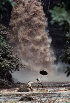 Two men try to cross a monsoon swollen river after the bridge was swept away, Goa, India.  Monsoon Season by Steve McCurry