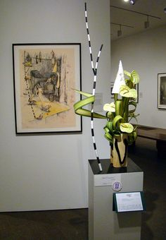DSC06457_1415 Gail Emmons - Orinda by godutchbaby, via Flickr. Gail Emmons of Orinda carefully, and literally, duplicated the black and white walking stick, Japanese wooden shoes, and wizard hat, but then added a wonderful dynamic element to her work by featuring the S-shaped Hala leaf to convey the bent figure in a more abstract way.