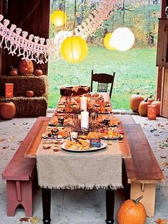 Set up a table in the barn for a festive Halloween or harvest party! Orange and white paper lanterns make perfect lighting! | Living the Country Life | http://www.livingthecountrylife.com/country-life/halloween-in-the-country/