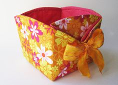 This basket was made to resemble paper origami boxes. The ends are embellished with large eyelets and wired ribbon. The back and the front look