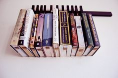 Custom made wooden book rack / bookshelf in Wenge. Pins also work as bookmarks. Bookcase. $210.00, via Etsy.