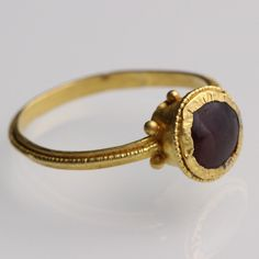 Jewelry Auction - NO RESERVE ITEM - Nov 30th 2016 - Byzantine Cup Bezel Ring. Possibly 6th-7th century. Flat band with a strip of beaded wire forming a ridge, joining at the shoulders a cup bezel with six globules at the base, decorated with beaded wire and set with a garnet cabochon.  This and more important art for sale on CuratorsEye.com
