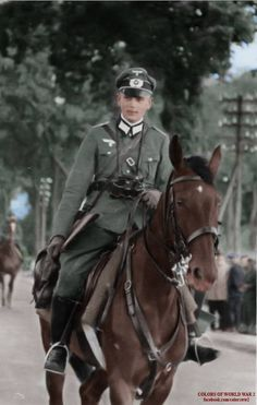 A Wehrmacht cavalry officer travels along a city street while on his patrol.