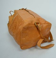 Gorgeous 1980s vintage leather backpack! Done in a lightweight tanned leather. Tooled design on the front pockets. Crossbody adjustable shoulder strap. Drawstring opening. Clean fully lined interior. Back zipper for entry into main pouch. Made in Paraguay!  Excellent Vintage Condition: A couple marks and scratches here and there, some light wear at bottom of bag. Overall, a gorgeous backpack!  MEASUREMENTS: circumference : up to 36 WIDTH across bottom : 10 HEIGHT : 16  * Overpayment…