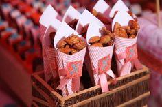 """Nesse aniversário em clima de festa de junina, as amêndoas caramelizadas foram colocadas em embalagens cônicas de papel listrado rosa com fita e cartão estampado com um """"N"""", letra inicial de Nina, a aniversariante"""