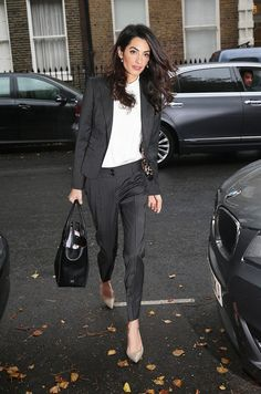 Amal Clooney wears a white shirt, pinstripe suit, nude heels, and a black leather tote bag