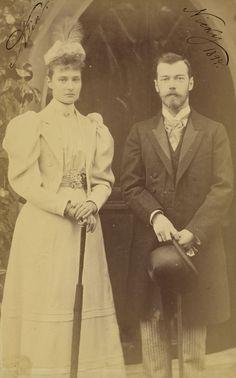 Czarevich Nicholas está de pé à direita, segurando um chapéu e uma bengala. Princesa Alix está de pé ao lado dele, à esquerda segurando um guarda-chuva dobrado e usando um chapéu decorado com uma pena. Eles estão de pé sobre um tapete modelado e há uma porta gótica por trás deles. A fotografia é assinada e datada 'Alix' e 'Nicky 1894' nos cantos superiores.