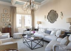 The living room's coffered ceiling is painted in Farrow & Ball's light blue. A Lee Industries sofa and a Samuel wing chair with nailhead trim by Hickory Chair join a wrought-iron coffee table by Lillian August for Hickory White. The wood-and-wrought-iron Rouleau chandelier is by Currey & Company.