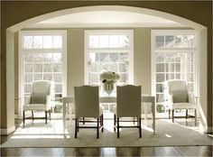 An archway opens to a sun filled dining room with taupe walls filled with a white lacquered dining table lined with linen side chairs and white linen host chairs over hardwood floors layered with an ivory rug. Taupe Walls, Pretty Room, Beautiful Interiors, Dining Chairs, Dining Rooms, Sunroom Dining, Sunroom Office, Side Chairs, Decoration