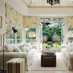 Arrange sofas facing each other and maximise the outdoor feel with botanical-print blinds and classic furniture and choose a matt floor in stone or ceramic so that it's easy to clean