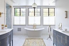 Stunning master bath features mismatched gray footed vanities accented with brass hardware and topped with white marble facing each other across from yellow rug atop mosaic tiled floor.