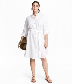 White. Shirt dress in soft linen with a collar, buttons at front, and a tie belt at waist. Long sleeves with buttoned cuffs.