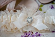 Custom garter - champagne garter and bow with cheesy fabric rose removed and an ostrich feather and earring attached to match the bride's  jewelry and feather hairpiece. Unique and vintage chic! Photo by Bradley Images.