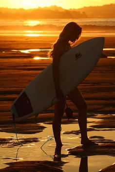 Surfer girl at sunset. Featured on Surfd.com in an article about why surfing should be a religion.