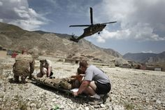 An injured U.S. Army soldier from the 4th Infantry Combat Division awaits to be medically evacuated by a Black Haw helicopter in Kunar's Pech Valley. (Photo by Sebastiano Tomado/SIPA USA)