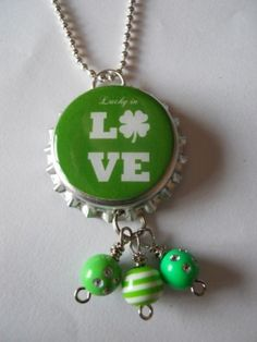 This is a St Patricks Day bottle cap necklace The image says LUCKY in LOVE br br The image is completely sealed with a thick resin that is very durable Bottle Cap Jewelry, Bottle Cap Necklace, Bottle Cap Art, Jar Lids, Jars, Lucky In Love, Clovers, Craft Storage, Wire Earrings