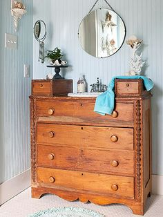 An old dresser is repurposed into a sink and vanity with lower drawers that offer plenty of storage options. A vintage mirror replaces a traditional medicine cabinet above the vanity.