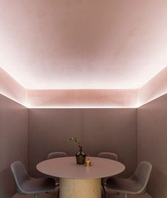 Inside, the main feature is the ceiling, which is coated in a light pink textured plaster and covered with a timber structure that forms frames around clay pots.
