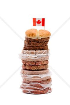 image of minced meat arranged over each other with a small canadian flag. - Close-up shot of raw minced meat arranged on top of each other with a Canadian flag on top against plain white background.
