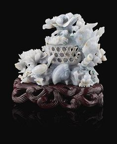 LAVENDER JADEITE CARVING in the form of a pierced basket containing a fish with a floriform and crab carved cover, with other fish and crabs amongst seaweed and lotus, the hardwood stand carved as waves 12cm tall (with stand)