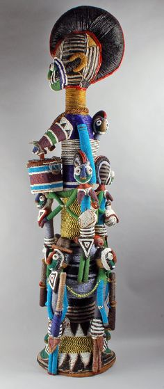 Africa | Figure group (possibly for ritual use) comprising of a women with other figures; glass beads on velvet and cloth with a basketry frame | Purchased in 1924 at the palace of the Ogoga of Ikerre-Ekiti