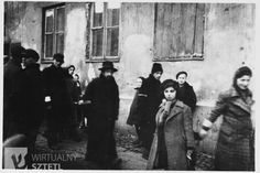 Jews wearing armbands are gathered outside a partially boarded-up building in the Warsaw ghetto