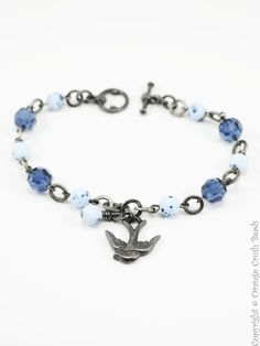 Bracelet 1435 -  	A cheerful navy blue and periwinkle beaded charm bracelet featuring a swooping swallow charm.
