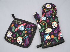 Day of the Dead oven mitt and pot holder. The oven mitt is lined with black fabric and has an inner layer of quilt batting in the top half. Both