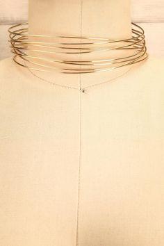 Les anneaux de Saturne flottent autour de son cou gracieux.  Saturn's rings float around its graceful neck. Cobro - Golden multi-row choker necklace www.1861.ca