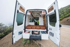 Back view of a sprinter van conversion with white interior and fold-down bed in the back for an awesome camper van conversion