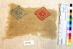 Fig. 22: Fragment. 9th–10th century. Cotton tabby embroidered with blue and red silk rhombi, Kumtura Canyon, Xinjiang, China. Turfan Collection, Berlin (III7596). © Staatliche Museen zu Berlin, Museum für Asiatische Kunst. Photograph by Mariachiara Gasparini.